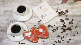 Saint Valentine`s Day concept. Coffee in white cups, home made heart shaped ginger biscuit on wooden background. hand. Saint Valentine s Day concept. Coffee in stock footage