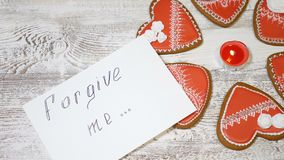 Saint Valentine`s Day. Love. Heart shaped ginger biscuits,on wooden background. hand drops a FORGIVE ME message note. Saint Valentine s Day. Love. Heart shaped stock video footage
