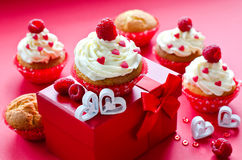 Saint Valentine's Day. Muffins for breakfast and gift box. Cupcakes for Valentine's Day with present box and fresh raspberries Stock Photography