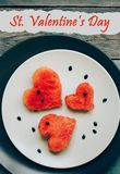 Saint Valentine\'s Day postcard, watermelon heart shape on the plate, wooden background. Top view stock image
