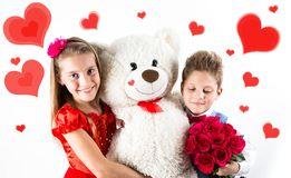 Saint Valentine`s day. Pretty girl with red dress and gentleman boy with blue vest, red butterfly tie, red roses bucket and heart