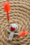 Saint Valentine thread doll. Saint Valentine toy made from white thread with a heart instead of mouth , on a rope background Royalty Free Stock Photos