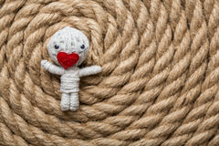 Saint Valentine thread doll. Saint Valentine toy made from white thread with a heart instead of mouth , on a rope background Royalty Free Stock Photo