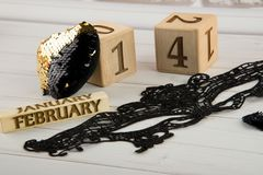Saint Valentines day composition. Wooden calendar, black lace mask and golden sequins heart royalty free stock image