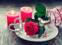 Saint Valentines's Day  with romantic table setting and rose. Rose on plate, candles and hearts on dark wooden background Stock Photos