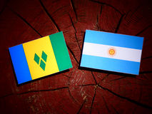 Saint Vincent and the Grenadines flag with Argentinian flag on a. Tree stump Royalty Free Stock Image