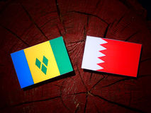Saint Vincent and the Grenadines flag with Bahraini flag on a tr. Ee stump Stock Photo
