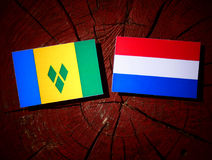 Saint Vincent and the Grenadines flag with Dutch flag on a tree. Stump isolated Royalty Free Stock Photo