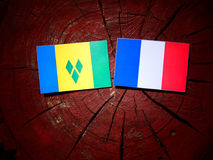 Saint Vincent and the Grenadines flag with French flag on a tree. Stump isolated Stock Images