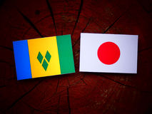 Saint Vincent and the Grenadines flag with Japanese flag on a tree stump isolated Stock Photography