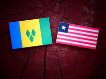 Saint Vincent and the Grenadines flag with Liberian flag on a tr. Ee stump isolated Royalty Free Stock Photo