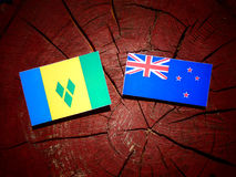 Saint Vincent and the Grenadines flag with New Zealand flag on a. Tree stump isolated Stock Photo