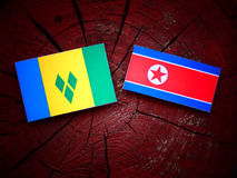 Saint Vincent and the Grenadines flag with North Korean flag on a tree stump  Royalty Free Stock Photos