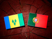 Saint Vincent and the Grenadines flag with Portuguese flag on a. Tree stump isolated Stock Images