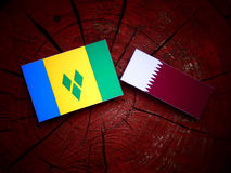 Saint Vincent and the Grenadines flag with Qatari flag on a tree stump isolated. Saint Vincent and the Grenadines flag with Qatari flag on a tree stump Stock Image
