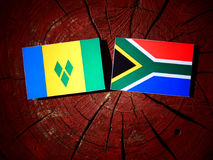 Saint Vincent and the Grenadines flag with South African flag on. A tree stump isolated Royalty Free Stock Photography