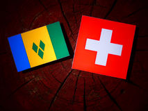 Saint Vincent and the Grenadines flag with Swiss flag on a tree. Stump isolated Stock Photo