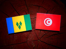 Saint Vincent and the Grenadines flag with Tunisian flag on a tr. Ee stump Stock Photo