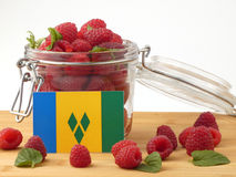 Saint Vincent and the Grenadines flag on a wooden panel with ras. Pberries isolated on a white background Stock Image