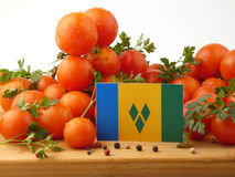 Saint Vincent and the Grenadines flag on a wooden panel with tom. Atoes isolated on a white background Stock Image