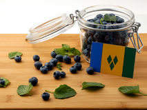 Saint Vincent and the Grenadines flag on a wooden plank with blu. Eberries  on white Royalty Free Stock Photos