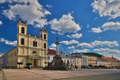 Saint Xavier Cathedral at Banska Bystrica. Saint Xavier Cathedral and plaque pillar at Banska Bystrica at Namestie SNP square during summer Stock Photography