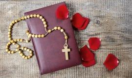 Sainte Bible, chapelet et pétales de rose rouges Photographie stock libre de droits