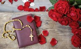 Sainte Bible, chapelet et pétales de rose rouges Images stock