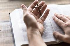 Sainte Bible de lecture jugeant une croix en bois disponible image stock