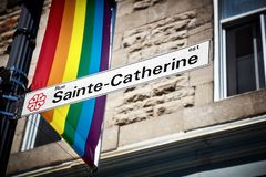 Sainte Catherine street sign and a rainbow gay pride flag. In gay village of Montreal, Canada royalty free stock photos