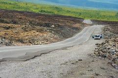 People enjoy the view from the asphalt road over volcanic lava of Piton de la fournaise volcano in Sainte-Rose De La Reunion, Fran stock photography