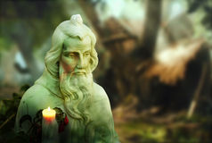 Saintly statue. Very old religous statue in garden setting with burning candle Royalty Free Stock Image