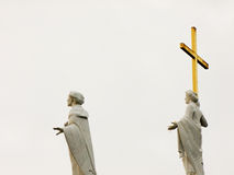 Saints looking to Sky. Monument of two saint People standing and watching to the Sky with Cross in Hands Royalty Free Stock Image