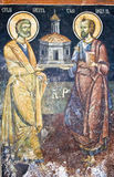 Saints in an old painting. A painting of two saints on the wall of an Orthodox Church Stock Photos