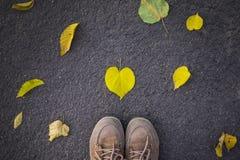 Saison d'automne, pieds dans des chaussures et feuille en forme de coeur au sol photos libres de droits