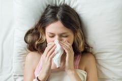 Saison de la grippe froide, écoulement nasal Fille malade sur le lit éternuant dans le mouchoir dans la chambre à coucher images libres de droits