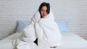 Saison de la grippe froide, ?coulement nasal Fille malade sur le lit ?ternuant dans le mouchoir dans la chambre ? coucher banque de vidéos
