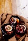 Saison- und Feiertagskonzept Weihnachtsglühwein mit schönen orange Scheiben innerhalb des Glases, bedeckt mit warmem weißem Schal lizenzfreie stockbilder