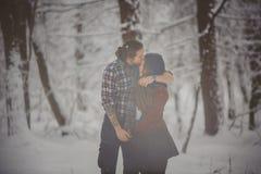 Saisontätigkeiten im Freien Liebevolle Paare der Lebensstilgefangennahme, die in Wald des verschneiten Winters gehen stockfotografie