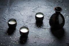 Saké dans la céramique noire sur la roche noire photo stock
