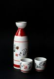 Sake. Two cups and a bottle of Japanese sake shot against a black background stock photo