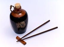 Sake and chopsticks. Brown bin sake and Japanese chopsticks Royalty Free Stock Photo