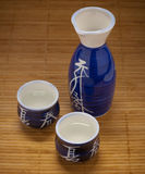 Sake flask and cups on bamboo Stock Photography