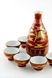Sake Serving Set. Dark red with gold detail sake serving set with pitcher and six cups Royalty Free Stock Photography