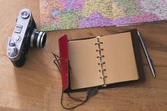 Saker för handelsresande` s: gammal kamera, översikt, anteckningsbok på en träbakgrund Royaltyfria Bilder
