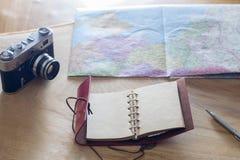 Saker för handelsresande` s: gammal kamera, översikt, anteckningsbok på en träbakgrund Arkivfoto