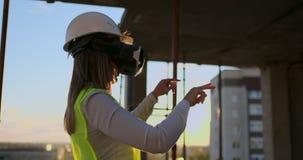 Sakkunnig tekniker Builder för kvinna i VR-exponeringsglas och hjälmkontroller framsteget av skyskrapakonstruktion som flyttar ha lager videofilmer