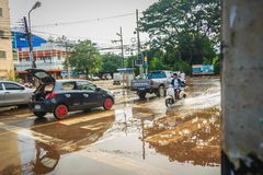 Sakon Nakhon, Thailand - August 3, 2017: After flood water reced. Ed, the sunk saloon car is recovering and pull by the towing pickup car to go to repair and Stock Photo