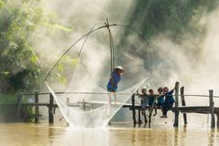 Rural man fishing by fishing net while group of rural children Royalty Free Stock Photos