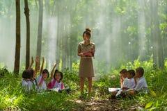 Beautiful teacher in uniform teaching her students outdoor class Stock Photo